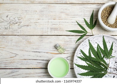 Flat lay composition with hemp leaves, seeds, cosmetic products and space for text on wooden background