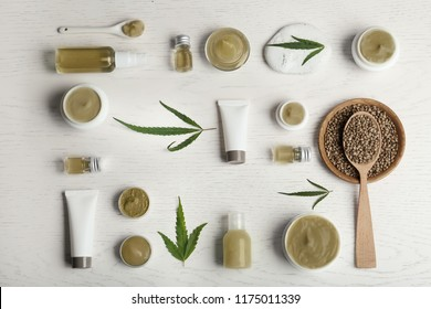Flat lay composition with hemp lotion on white wooden background