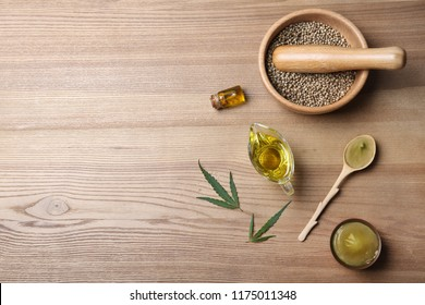 Flat lay composition with hemp lotion and space for text on wooden background