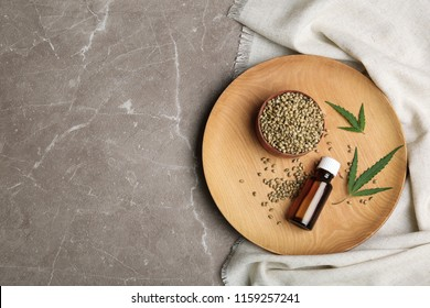 Flat lay composition with hemp seeds, bottle of extract and space for text on grey background