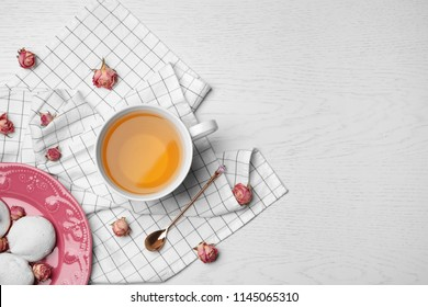 Flat lay composition with hot tea, meringues and flowers on table