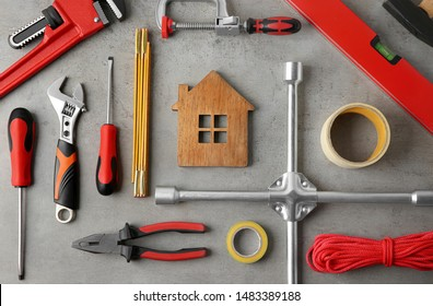 Flat lay composition with house figure and repair tools on grey stone table