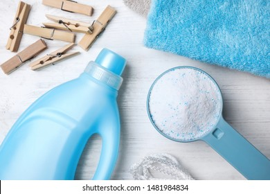Flat lay composition with laundry detergents, clothespins and towels on white wooden background
