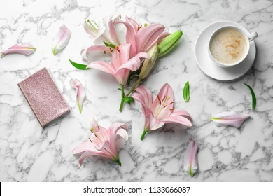 Flat lay composition with lily flowers, cup of coffee and notebook on marble background
