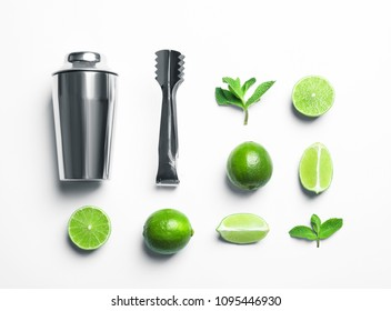 Flat lay composition with lime, mint and shaker on light background. Refreshing beverage ingredients