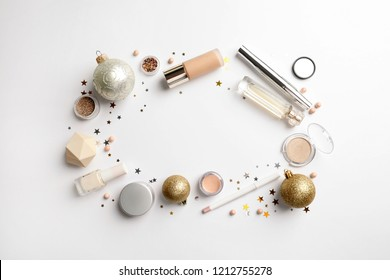 Flat lay composition with makeup products and Christmas decor on white background. Space for text