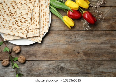 Flat lay composition with matzo and flowers on wooden background, space for text. Passover (Pesach) Seder