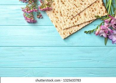 Flat lay composition of matzo and flowers on wooden background, space for text. Passover (Pesach) Seder