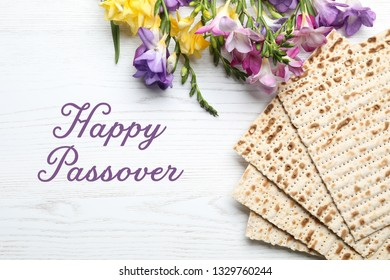 Flat lay composition of matzo and flowers on wooden background. Happy Passover (Pesach)