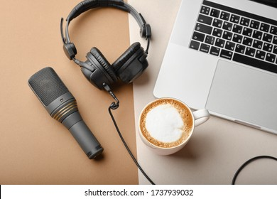 Flat lay composition with Microphone for podcasts  and black studio headphones on brown background with coffee and laptop, learning online education concept.