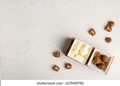 Flat lay composition with milk and coffee ice cubes on white wooden background. Space for text