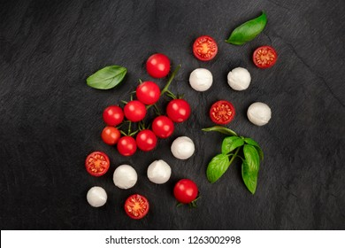 A flat lay composition with Mozzarella cheese, cherry tomatoes and basil leaves on a dark background, Italian cuisine ingredients with a place for text