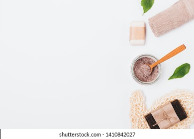 Flat lay composition of natural coffee scrub and cleansing soap with washcloth next to green leaves on white background with copy space.