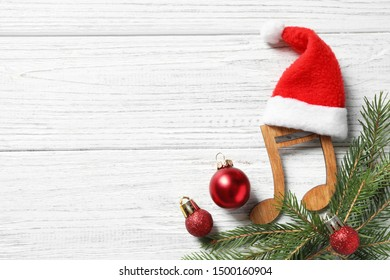 Flat lay composition with note on white wooden background, space for text. Christmas music concept