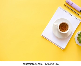 flat lay composition with notebook, pen, coffee, plant on yellow background. Concept remote study and work at home, freelance, quarantine, office table, coffee break. Distance learning. Copyspace