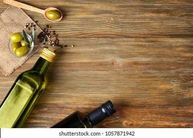 Flat lay composition with olives and oil on wooden background