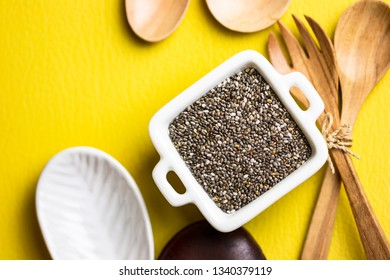 Flat lay composition on yellow table top with Chia seeds / superfood for healthy lifestyle concept