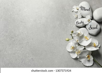 Flat lay composition of orchid flowers and zen stones with words Mind, Body, Soul on light background. Space for text