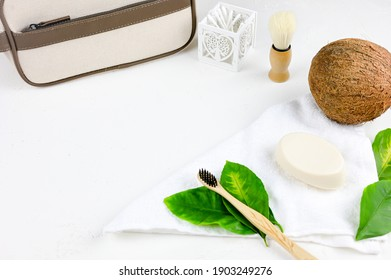 Flat lay composition with organic body care products and space for text on light background. Cosmetic products, toiletries for hygiene. Bath items with teeth brush, soap, coconut.