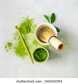 Flat lay of composition with organic Japanese green tea and tools Chasen bamboo whisk, Chashaku spoon and bowl for brewing background with copy space.