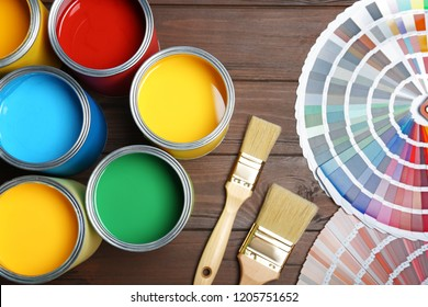 Flat lay composition with paint cans, brushes and color palettes on wooden background