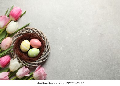 Flat lay composition with painted Easter eggs in wicker nest and tulips on color background, space for text