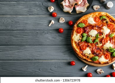 Flat lay composition with pizza and ingredients on wooden background