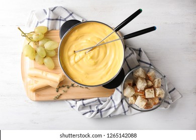 Flat lay composition with pot of delicious cheese fondue on wooden table