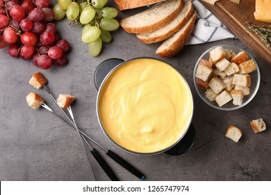 Flat lay composition with pot of delicious cheese fondue on gray table