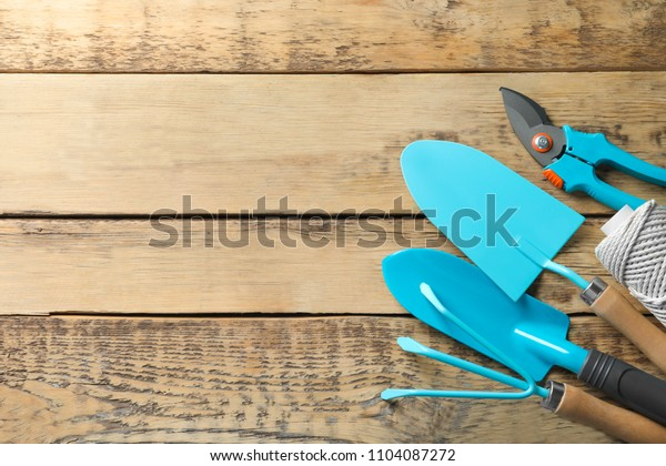 Flat lay composition with professional gardening tools on wooden background