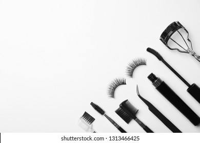 Flat lay composition of professional makeup tools and false eyelashes on white background