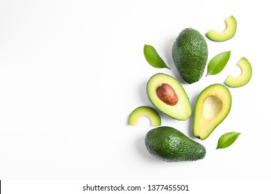 Flat lay composition with ripe avocados and leaves on white background, space for text