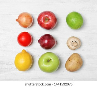 Flat lay composition with ripe fruits and vegetables on white wooden table