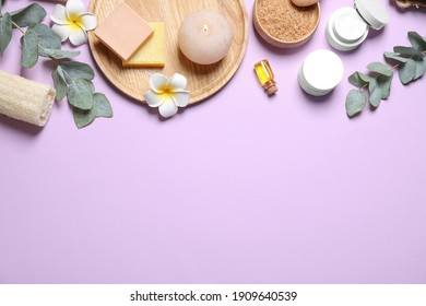 Flat lay composition with salt and cosmetic products on violet background. Space for text