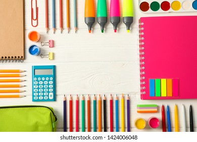 Flat lay composition with school supplies on wooden background, space for text