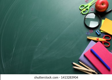 Flat lay composition with scissors and school supplies on chalkboard. Space for text
