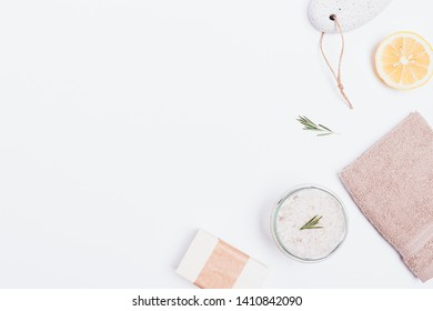 Flat lay composition of sea salt with rosemary, soap and fresh lemon next to a towel and pumice stone on white background with copy space.