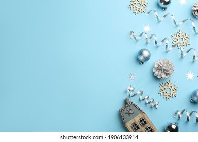 Flat lay composition with serpentine streamers and Christmas decor on light blue background. Space for text