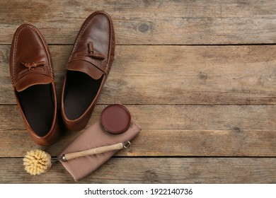 Flat lay composition with shoe care accessories and footwear on wooden background. Space for text