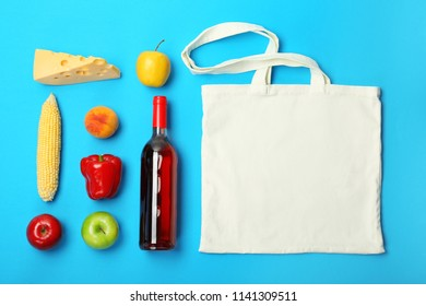 Flat lay composition with shopping bag and products on color background