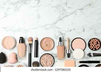 Flat lay composition with skin foundation, powder and beauty accessories on marble background. Space for text