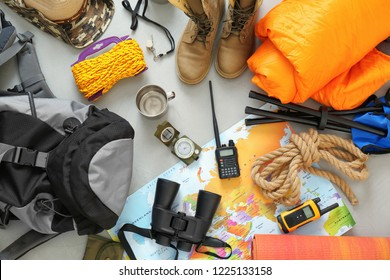 Flat lay composition with sleeping bag and camping equipment on grey background