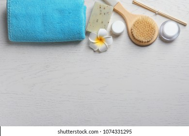 Flat lay composition with spa cosmetics and towel on wooden background