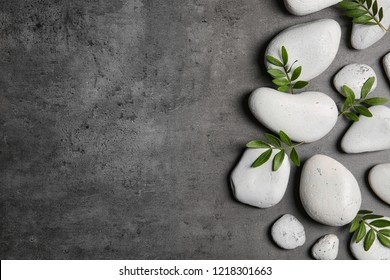 Flat lay composition with spa stones and bamboo leaves on grey background. Space for text