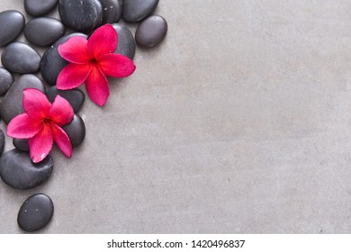 Flat lay composition with spa stones, exotic red flowers and space for text on grey background