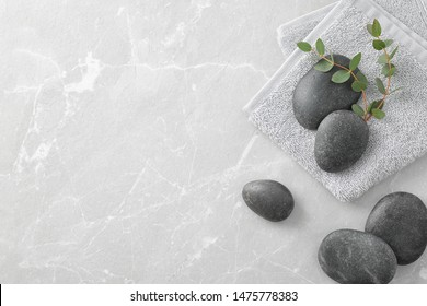 Flat lay composition with spa stones and green leaves on grey table, space for text
