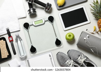 Flat lay composition with sport equipment and scales on light background. Weight loss