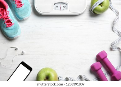 Flat lay composition with sport items, scales and space for text on wooden background. Weight loss concept