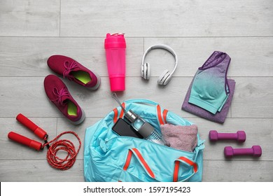 Flat lay composition with sports bag on wooden background