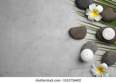 Flat lay composition with stones on grey background, space for text. Zen concept